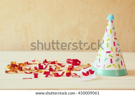 Party hat next to colorful confetti on wooden table - stock photo