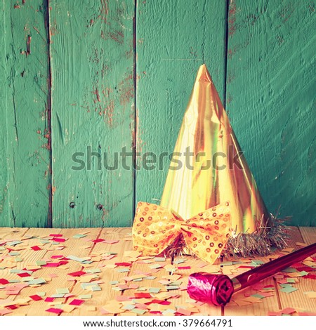 party hat next to pink party whistle on wooden table with colorful confetti. vintage filtered image - stock photo
