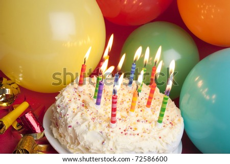 Party hats, blower and streamers and cake  on red background - stock photo