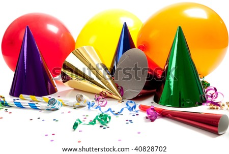 Party hats, noise makers, streamers, balloons and confetti on a white background - stock photo