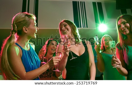 party, holidays, celebration, nightlife and people concept - happy young women with glasses of champagne in club - stock photo