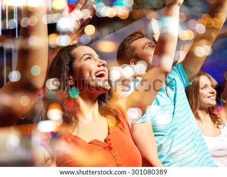 party, holidays, celebration, nightlife and people concept - smiling friends waving hands at concert in club - stock photo