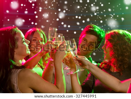 party, holidays, celebration, nightlife and people concept - smiling friends with glasses of non-alcoholic champagne in club - stock photo