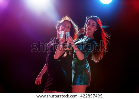 Party, holidays, celebration, nightlife and people concept - smiling young beautiful girls dancing in club - stock photo