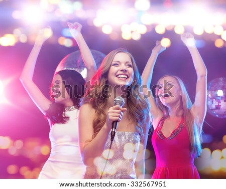party, holidays, nightlife, entertainment and people concept - concept - happy women with microphone singing karaoke and dancing at night club - stock photo