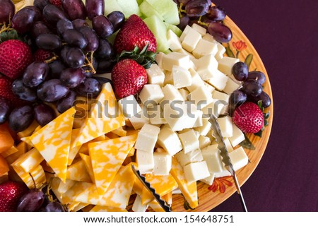 Party hors d'oeuvre platter of assorted cheeses and fruits from above - stock photo