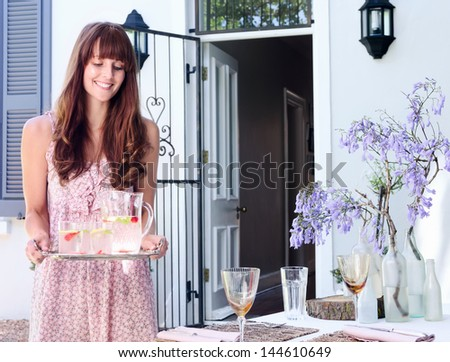 Party hostess carries a tray of drinks to the table in a domestic garden environment - stock photo