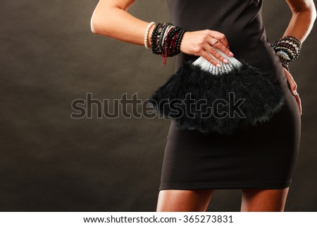 Party new year celebration and carnival concept. Beauty woman wearing evening dress with black feather fan in hand - stock photo