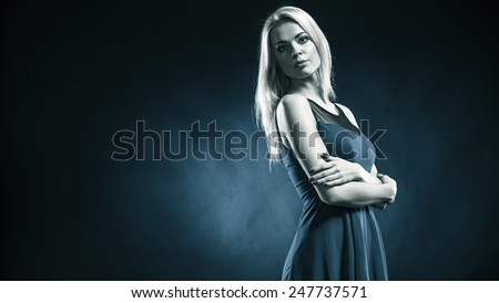 Party, new year, celebration, disco concept - Portrait attractive fashion woman, blonde long hair girl in evening dress night club dark blue background - stock photo