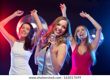 "party, ""new year"", celebration, friends, bachelorette party, birthday concept - three women in evening dresses dancing and singing karaoke - stock photo"