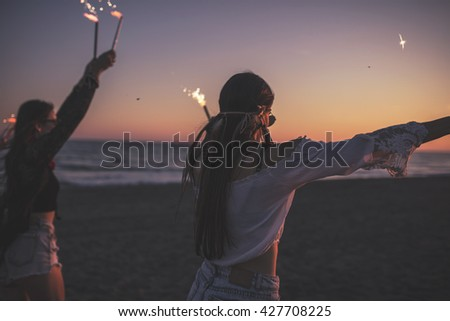 Party on the Beach by night. Leisure Happiness Concept. Silhouette of two friends with firecracker  - stock photo