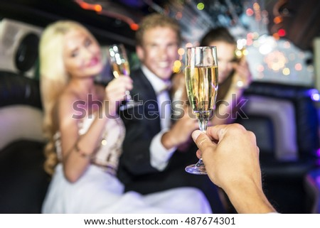 Party people toasting with glasses of champagne inside a limousine