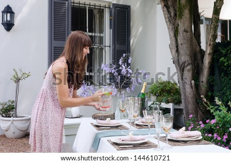 Party planner organising water for the table with simple place settings in a domestic garden environment - stock photo