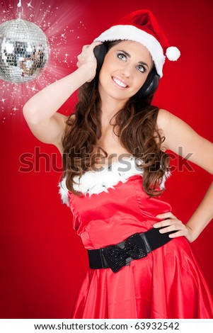 Party Santa girl listening music on red background - stock photo