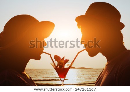 party time, couple drinking cocktail together on the beach during their honeymoon - stock photo