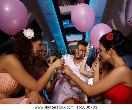 Party time in limo with young females and handsome man. - stock photo