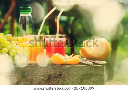 Party Time Outdoor. Fruits and Glasses of Fresh Juice on the Wooden Table - stock photo