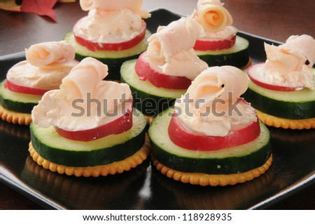 Party tray of cucumber, radish, cream cheese and ham canapes - stock photo