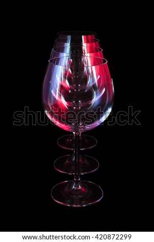 Party wine glasses in nightclub lit by red, blue, lilac lights, nightlife and entertainment industry, objects in row isolated on black background  - stock photo