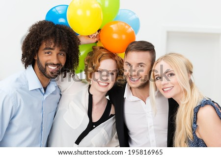 Partytime at the office with a group of rather dishevelled young business peole smiling and laughing at the camera while holding a large bunch of colorful balloons - stock photo