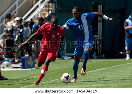 PASADENA, CA - JULY 7: Tosaint Ricketts #9 of Canada & Yoann Arquin #11 of Martinique during the 2013 CONCACAF Gold Cup game between Canada & Martinique on July 7, 2013 at the Rose Bowl in Pasadena. - stock photo