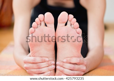 Paschimottanasana or seated forward bend yoga pose - holding feet detail - stock photo