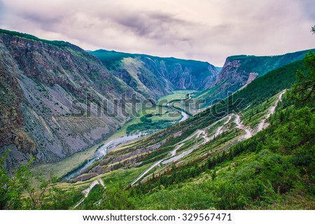 pass in a mountain valley with a river - stock photo