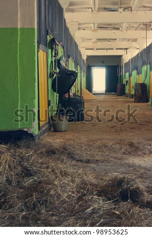 passage of the stable, saddle, hay and a bucket with water - stock photo