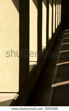 Passageway with sunlight and shadow outside building on college campus in southern California (focus on nearest stucco column) - stock photo