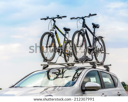 Passanger car with two bicycle mounted to the roof - stock photo