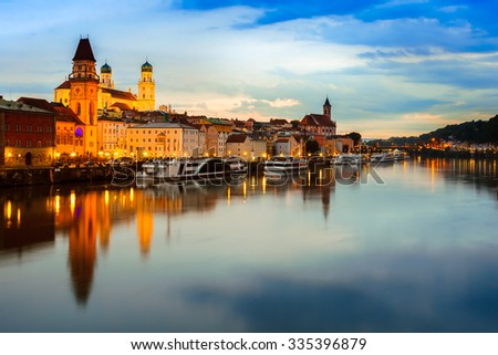 Passau from the Danube, Germany. View of the town at sunset with beautiful reflections and lights. - stock photo