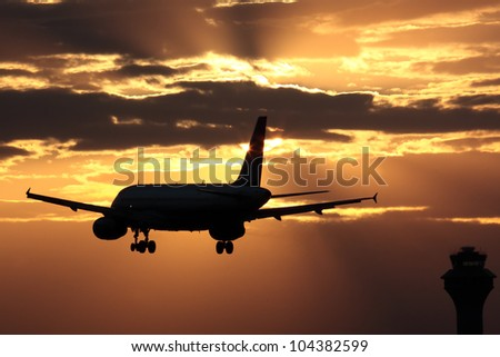 Passenger aircraft landing with dramatic sky in front - stock photo