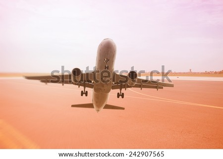 Passenger Airline taking off from airport in sunset - stock photo