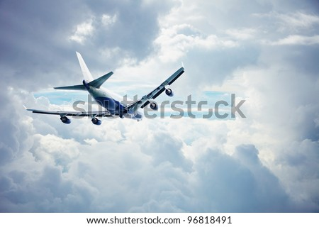 Passenger airliner flying through the thick clouds - stock photo