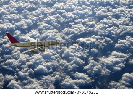 Passenger airliner over clouds - stock photo