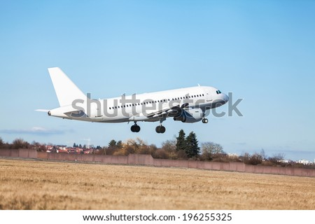 Passenger airliner taking off at an airport lifting clear of the runway in front of the terminal buildings, side view - stock photo