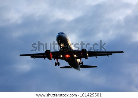 Passenger Airplane coming in for landing on cloudy evening - stock photo