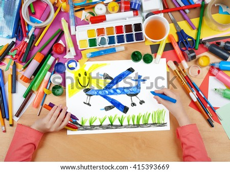 passenger airplane fly under sun child drawing, top view hands with pencil painting picture on paper, artwork workplace - stock photo