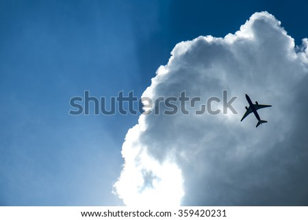 Passenger airplane in the clouds and sun-ray - stock photo