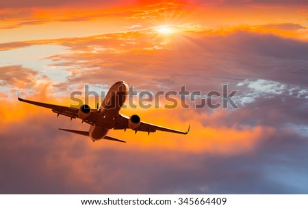passenger airplane in the clouds at sunset - stock photo