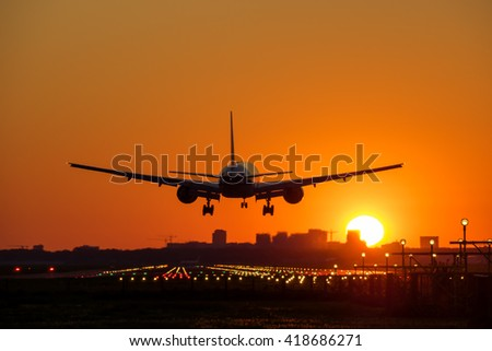 Passenger airplane is landing with a city skyline at the background. Sun is rising.