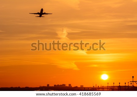 Passenger airplane is taking off with a city skyline at the background. Sun is rising.  - stock photo