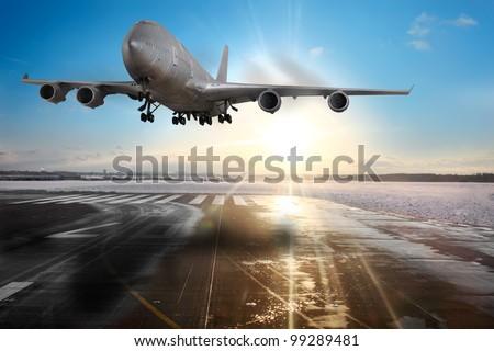 Passenger airplane landing on runway in airport. Evening - stock photo
