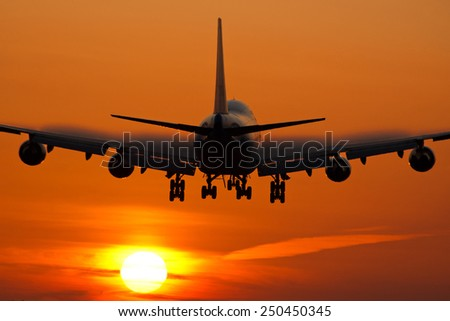 Passenger airplane landing while the sun is rising. - stock photo