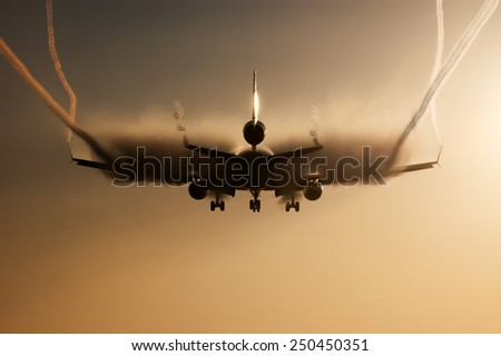 Passenger airplane landing while the sun is rising - stock photo
