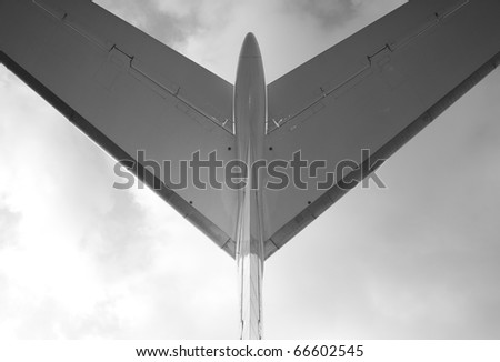 Passenger airplane, view with behind, black and white photo - stock photo