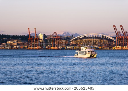 Passenger boat catamaran with several decks and cabins in the bay on the Pacific coast on the background of an industrial zone in the Port of Seattle - stock photo
