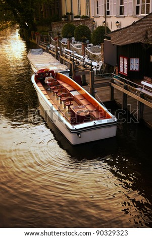Passenger boat docks at the pier at the canal in the evening - stock photo