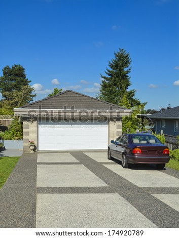 Passenger car parked on bar colored concrete driveway nearby double garage.  - stock photo