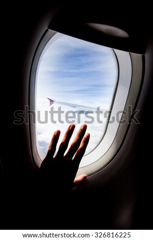 passenger hand touch window of airplane,silhouette - stock photo
